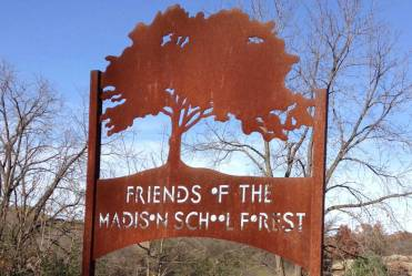 An large iron sign with a profile of a sprawling oak tree and the words Friends of the Madison School Forest