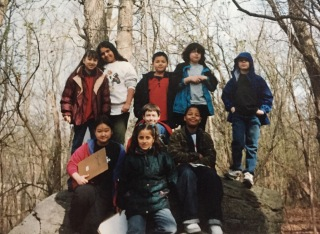 Nine fourth graders on top of a very large stone that was left behind when the glacier melted