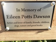 "The plaque reads ""In Memory of Eileen Potts Dawson - Artist and lover of family, friends, children, dogs, nature and great books"". It's on a bench on the Friends' Prairie."