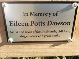 """The plaque reads """"In Memory of Eileen Potts Dawson - Artist and lover of family, friends, children, dogs, nature and great books"""". It's on a bench on the Friends' Prairie."""