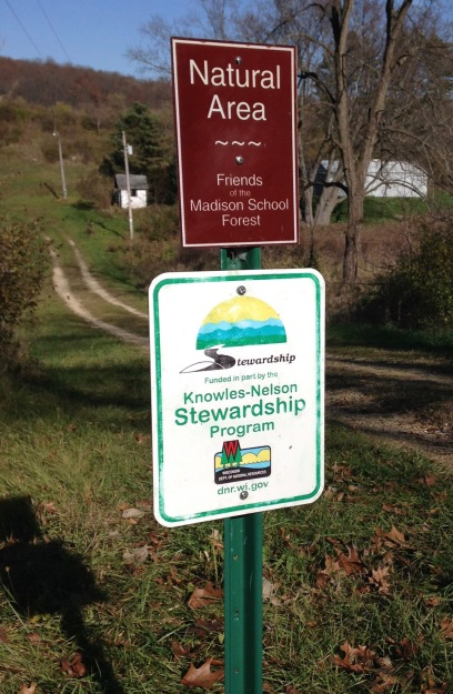 """Two signs on a post that mark the drive into the Friends Property. One says """"Natural Area - Friends of the Madison School Forest"""" and the other says """"Stewardship funded in part by the Knowles-Nelson Stewardship Program, Wisconsin Department of Natural Resources"""""""